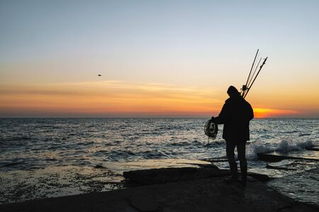 Photo pour Silhouette of man fisherman wearing coat, holding rod, fishing at the beach - image libre de droit