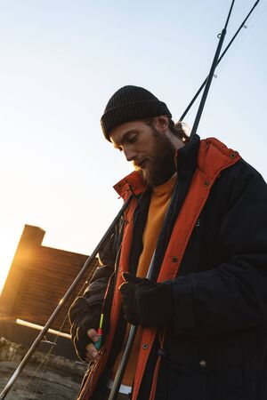 Photo pour Handsome brutal bearded fisherman wearing coat standing with a fishing rod at the seashore - image libre de droit