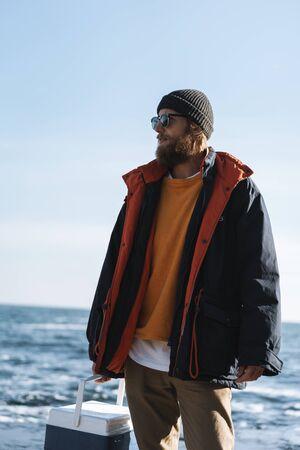 Photo pour Fisherman wearing coat standing at the seashore, carrying cooler - image libre de droit