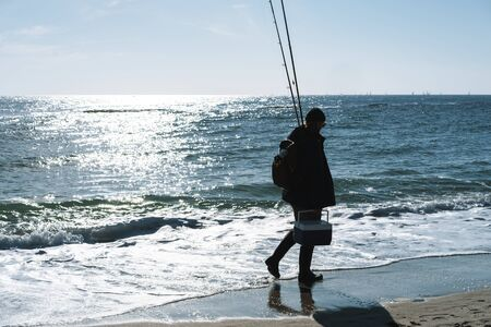 Photo pour Image of a handsome concentrated young man fisherman wearing coat and hat at the seashore. - image libre de droit