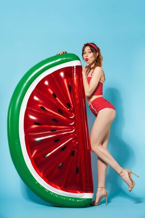 Photo pour Image of a beautiful young pin up pretty summer girl in swimwear posing isolated over blue background with watermelon air-matress bed. - image libre de droit