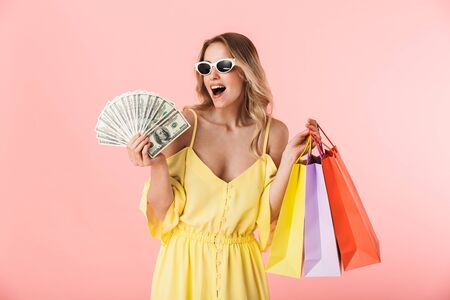 Photo for Image of a beautiful excited happy young blonde woman posing isolated over pink wall background holding shopping bags and money. - Royalty Free Image