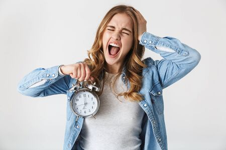 Photo pour Attractive screaming young girl standing isolated over white background, showing alarm clock - image libre de droit