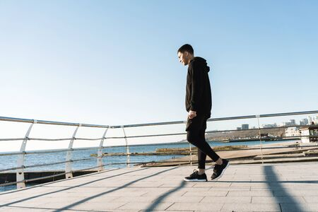 Photo pour Photo of joyful guy 20s in black clothes walking along wooden boardwalk by seaside after morning workout - image libre de droit