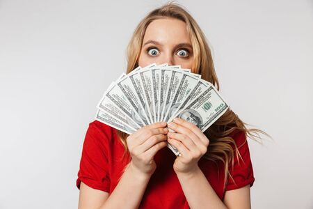 Photo pour Image of excited young pretty beautiful woman posing isolated over white wall background holding money. - image libre de droit