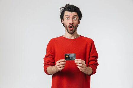 Handsome excited young bearded brunette man wearing sweater standing isolated over white background, showing credit card