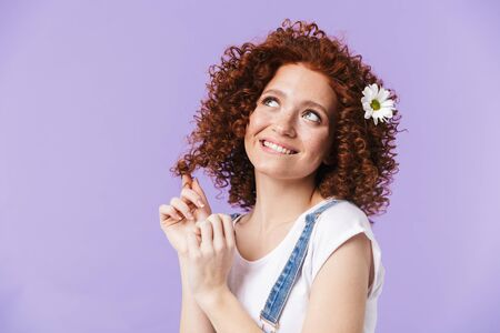 Photo pour Image of a beautiful curly happy redhead girl posing isolated over purple background with flowers in hair. - image libre de droit