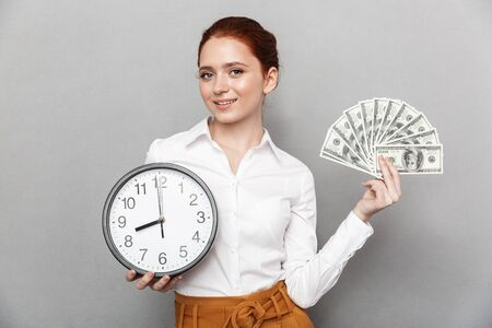 Photo pour Image of cheerful redhead businesswoman 20s in formal wear holding big clock and bunch of money cash isolated over gray background - image libre de droit