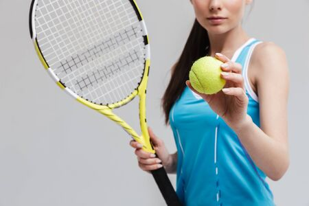 Foto de Cropped image of a confident woman tennis player holding racket and ball isolated over gray background - Imagen libre de derechos