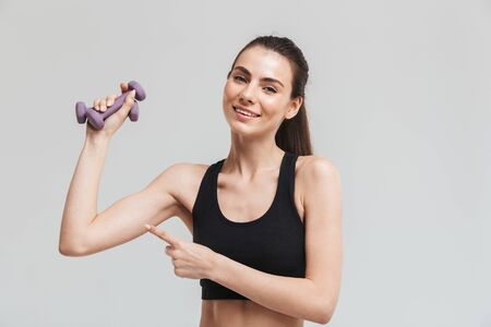 Photo for Image of a beautiful young sport fitness woman make exercises with dumbbells isolated over grey wall background. - Royalty Free Image