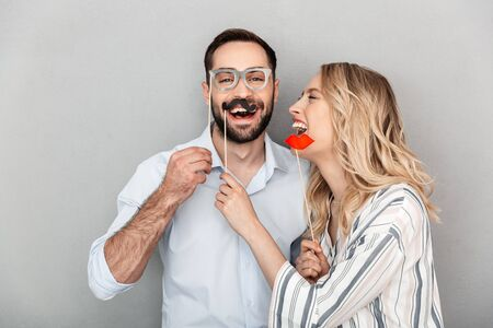 Photo for Photo closeup of pretty couple in casual clothing having fun with paper fake eyeglasses and mustaches on stick isolated over gray wall - Royalty Free Image