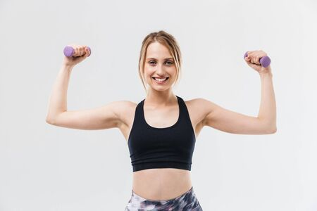Photo for Image of young blond woman 20s dressed in sportswear working out and doing exercises with dumbbells during fitness in gym isolated over white wall - Royalty Free Image