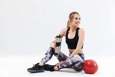 Foto für Image of european blond woman 20s dressed in sportswear working out and doing exercises with fitness ball during aerobics isolated over white wall - Lizenzfreies Bild