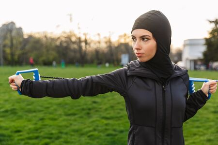 Foto de Image of a young serious strong muslim sports fitness woman dressed in hijab and dark clothes outdoors in green nature park make exercises with equipment expander. - Imagen libre de derechos