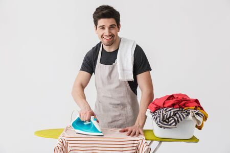 Foto de Handsome brunette houseman wearing apron standing isolated over white background, ironing clothes on a board - Imagen libre de derechos