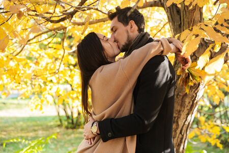 Photo pour Cheerful young couple spending fun time at the park in autumn, embracing, kissing - image libre de droit