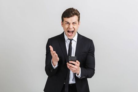 Foto für Image of angry yong businessman in formal suit typing on cellphone and screaming at camera isolated over gray background - Lizenzfreies Bild