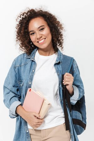 Photo pour Portrait of a pretty cheerful casual african girl carrying backpack standing isolated over white background, holding textbooks - image libre de droit