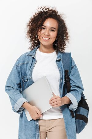 Photo pour Portrait of a pretty cheerful casual african girl carrying backpack standing isolated over white background, holding laptop computer - image libre de droit