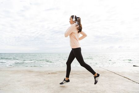 Photo pour Full length side view of an attractive young asian fitness woman jogging at the beach, listening to music with headphones - image libre de droit