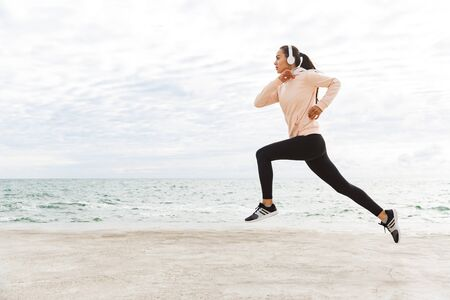 Photo pour Attractive young asian sportswoman exercising at the seashore, running, wearing headphones - image libre de droit
