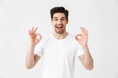 Foto de Portrait of a cheerful young man wearing casual clothing isolated over white background, ok - Imagen libre de derechos