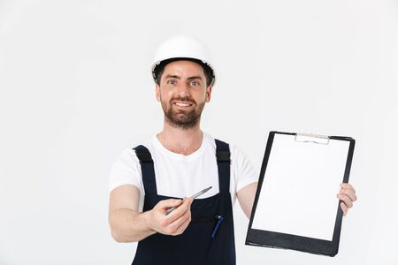 Photo pour Confident bearded builder man wearing overalls and hardhat standing isolated over white background, showing blank tablet - image libre de droit