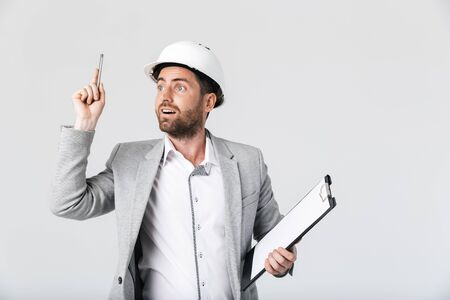 Photo pour Confident bearded man builder wearing suit and hardhat standing isolated over white background, holding blank notepad, pointing finger up - image libre de droit