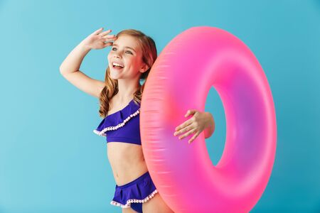 Foto de Cheerful little girl wearing swimsuit standing isolated over blue background, playing with inflatable ring - Imagen libre de derechos