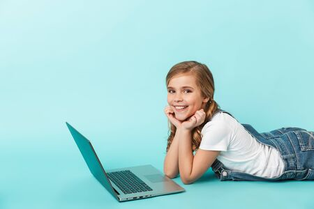 Foto de Portrait of a cheerful little girl isolated over blue background, studying with laptop computer - Imagen libre de derechos