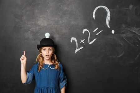 Photo for Image of pretty happy young little school girl posing isolated over chalkboard wall background have an idea. - Royalty Free Image