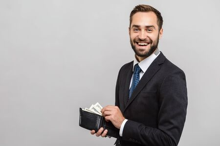 Photo pour Attractive happy young businessman wearing suit standing isolated over gray background, showing wallet full of money banknotes - image libre de droit