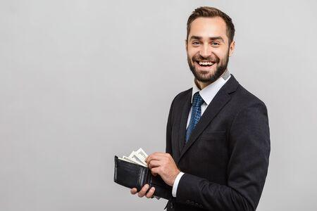 Foto de Attractive happy young businessman wearing suit standing isolated over gray background, showing wallet full of money banknotes - Imagen libre de derechos