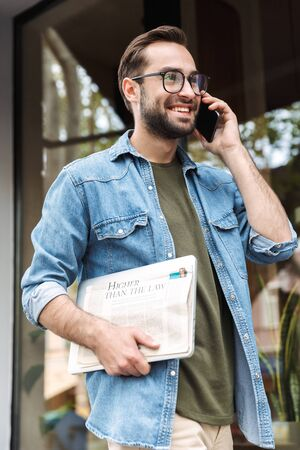 Foto de Photo of intelligent young man wearing eyeglasses talking on smartphone while walking through city street with newspaper and laptop in hand - Imagen libre de derechos