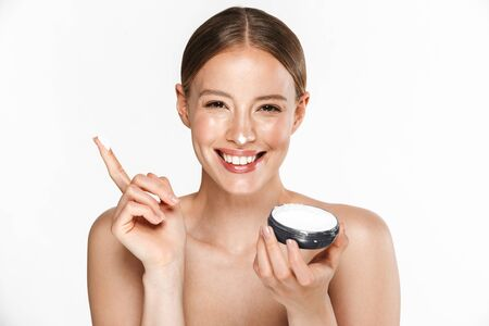 Foto de Image of a happy beautiful young amazing woman posing isolated over white background wall holding cream take care of her skin. - Imagen libre de derechos