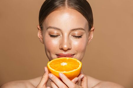 Photo pour Image of a beautiful pleased young amazing woman posing isolated over brown chocolate background wall holding orange. - image libre de droit