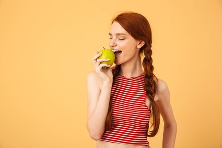 Photo for Image of a happy young beautiful redhead woman posing isolated over yellow background eat apple. - Royalty Free Image