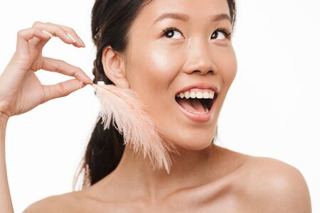 Photo for Image of a happy excited young beautiful asian woman posing isolated over white wall background holding feather. - Royalty Free Image