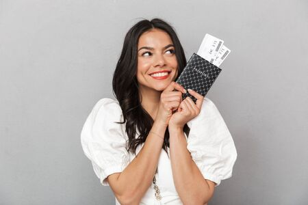 Photo pour Portrait of a beautiful young brunette woman wearing summer outfit standing isolated over gray background, showing passpport with flight tickets - image libre de droit