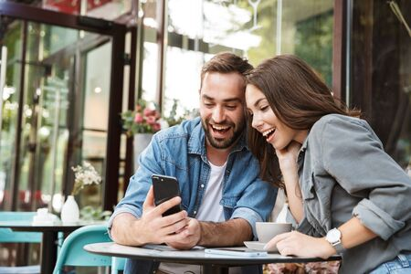 Foto de Attractive young couple in love having lunch while sitting at the cafe table outdoors, using mobile phone - Imagen libre de derechos