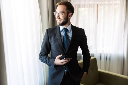 Photo pour Attractive smiling young businessman wearing suit standing at the hotel room, using mobile phone - image libre de droit