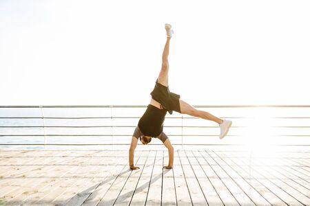 Foto de Photo of handsome strong young sports man at the beach near sea standing on arms hands make yoga cartwheel exercises. - Imagen libre de derechos