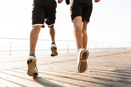 Foto für Back view half portrait of two young healthy sportsmen jogging outdoors at the beach - Lizenzfreies Bild