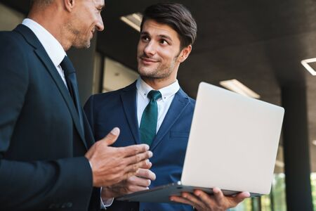 Foto de Portrait of successful businessmen partners dressed in formal suit standing outside office center and using laptop together during working meeting - Imagen libre de derechos