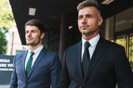 Photo pour Portrait closeup of two entrepreneur businessmen partners dressed in formal suit walking together outside job center during working meeting - image libre de droit