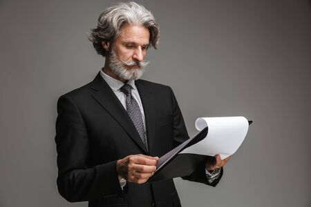 Photo pour Image of caucasian adult businessman wearing formal black suit holding paper charts isolated over gray background - image libre de droit