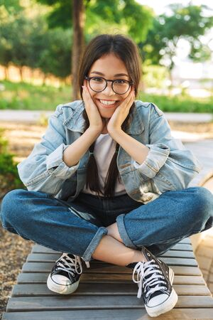 Foto de Photo of a pleased happy cute young student girl wearing eyeglasses sitting on bench outdoors in nature park. - Imagen libre de derechos