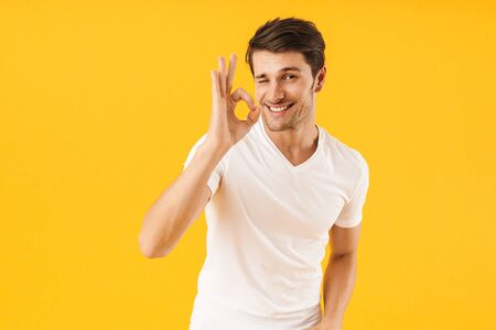 Photo for Photo of happy man in basic t-shirt smiling at camera while showing ok sign isolated over yellow background - Royalty Free Image