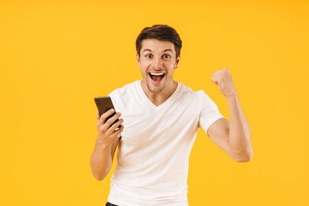 Photo for Image of a screaming happy shocked young man in casual white t-shirt using mobile phone isolated over yellow background make winner gesture. - Royalty Free Image