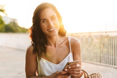Photo pour Portrait of happy woman in summer dress smiling at camera and holding cellphone while walking outdoors - image libre de droit